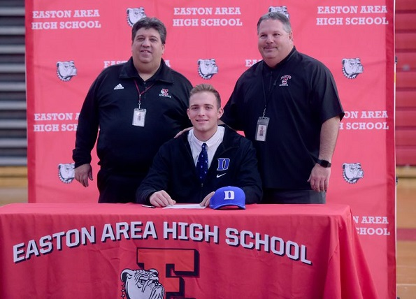 Easton High School baseball player Luke Storm signs his letter of intent for Duke University last December while surrounded by coaches Greg Hess (left) and Carm LaDuca (right). (Amy Shortell/The Morning Call)